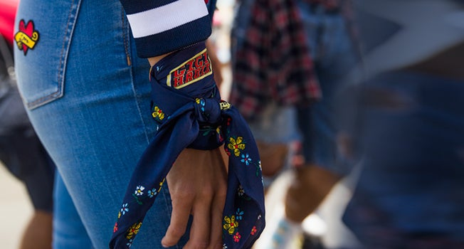 Inset of female model wearing Gigi Hadid-branded denim jeans and scarf tied at her wrist.