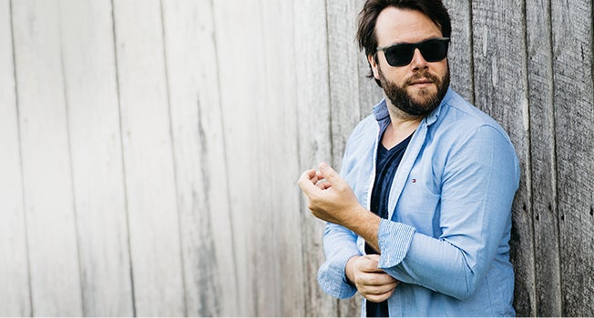 Matthew Chambers of blog Brothers and Craft wearing a dark blue v-neck tee, a light blue shirt and sunglasses.