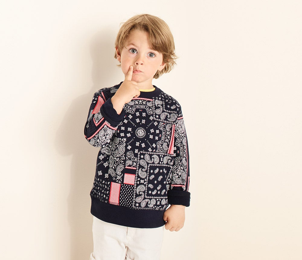 Standout sweaters. Patched prints and pale pastel accents for spring. Child wears printed sweater and chino shorts.