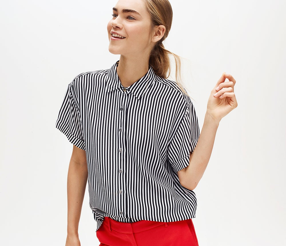 That works. Buttoned-up polish, buttoned-down vibe. Female model in stripe blouse.
