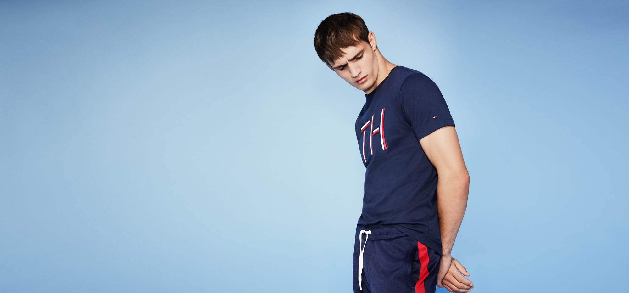 Urban sport. Bold colors and streamlined graphics hit the street. Male model wearing signature tee and athletic pants.
