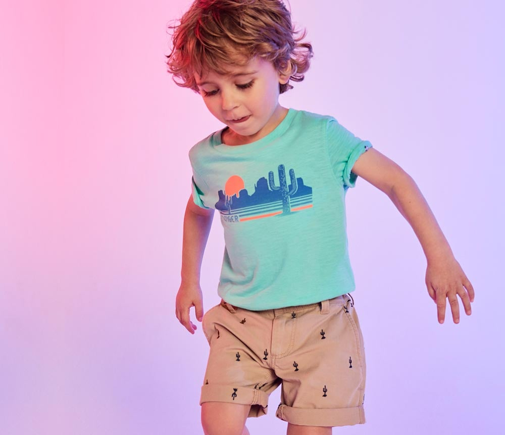Child in t-shirt with cactus graphic and cactus print shorts