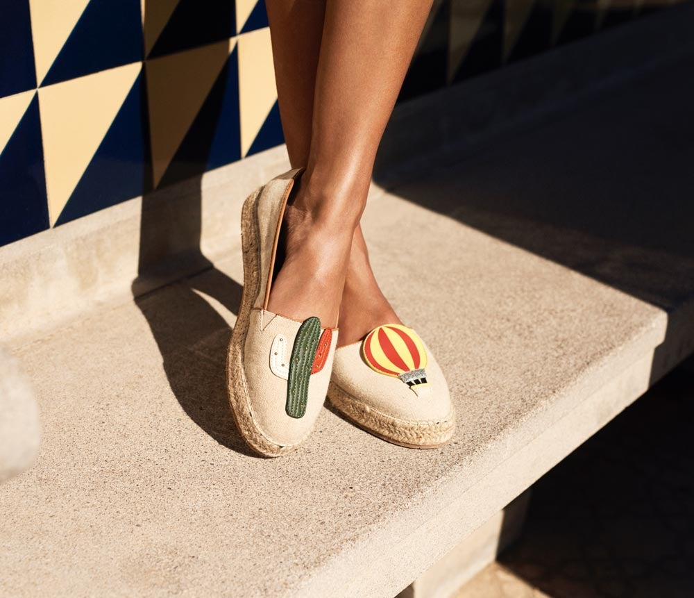 HAPPY FEET. Special touches guaranteed to put a spring in your step. Pair of women's espadrilles with cactus graphic on one shoe and hot air balloon graphic on the other.