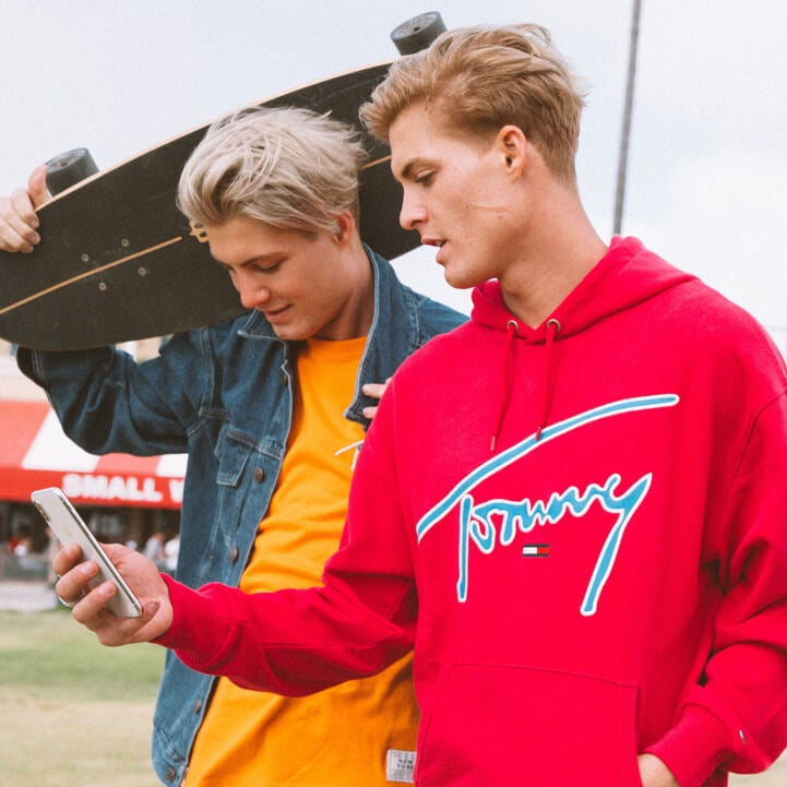 Two male models, one model wearing Tommy Hilfiger jacket and XPLORE t-shirt and other model wearing XPLORE sweatshirt holding a cell phone.