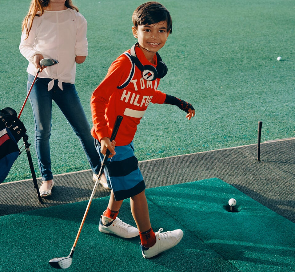 Swing Time. Easy-dress clothing means more time for play time. Child wears signature Tommy t-shirt and striped shorts, specially designed for ease of dressing.